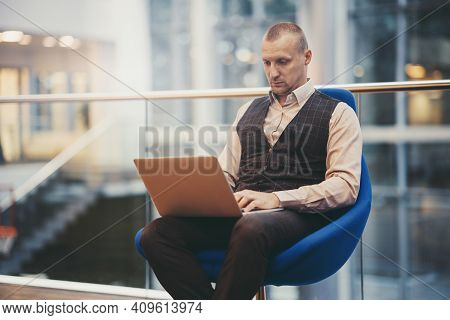 A Serious Mature Man Entrepreneur Is Sitting On An Armchair In An Office Hall And Sending An E-mail