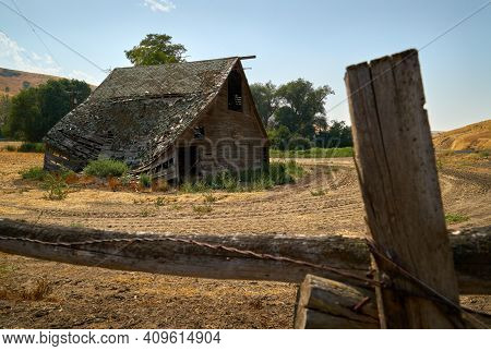 Derelict Wooden Barn. An Old, Abandoned, Vintage Wooden Barn In A Field.