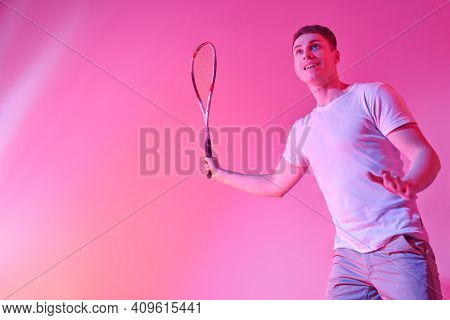 Excited sporty man playing squash with pleasure. Active lifestyle. Sports and healthcare. Studio portrait. Copy space.
