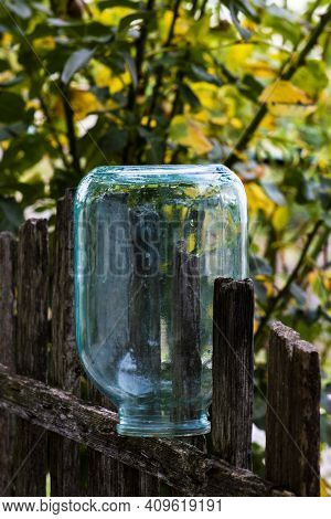 A Three-litre Glass Jar On A Wooden Fence. Front View On A Sunny Summer Day.