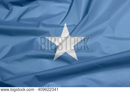 Fabric Flag Of Somalia. Crease Of Somalian Flag Background, A Single White Five-pointed Star Centere