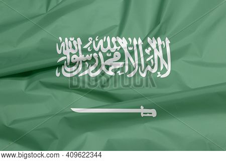 Fabric Flag Of Saudi Arabia. Crease Of Saudi Arabian Flag Background, A Green Field With The Shahada