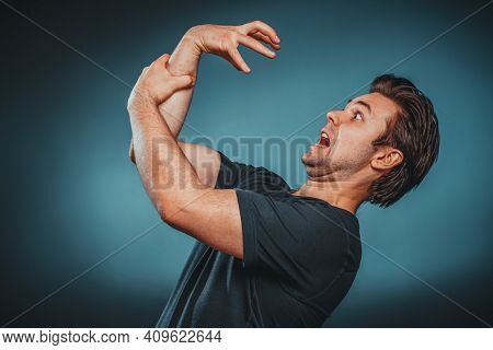 Scared man holding his hand that attacks him.