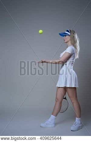Portrait Of Sportive And Young Woman With Racquet In White Sportswear With Cap Throwing Tennis Ball