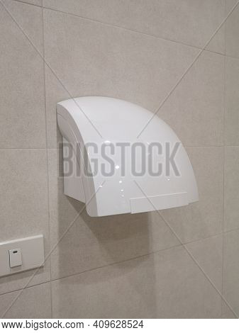 Hot Air Blower Dryer Wet Hand Modern Electric White Color On Brown Tiled Wall In Public Restroom, Wc