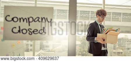 Company Closed On Windows Of An Empty Office With Business Man Packing Beloning Walking Out Of Busin