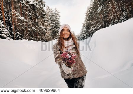 A Girl In A Sweater In Winter With A Bouquet In Her Hands Stands Among Large Snowdrifts