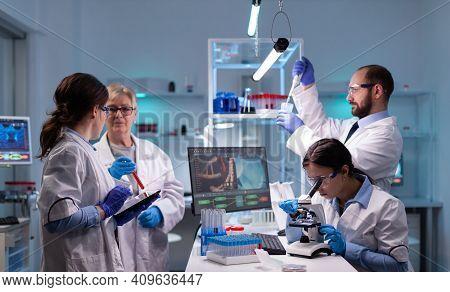 Team Of Scientific Investigators Conducting Experiments In Lab Using Microscope And Micropipette. La