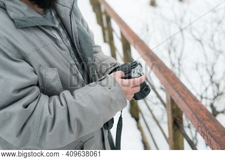 Photographer Using Camera Outside In Winter. Man Making Adjustments To Photographic Equipment, Close