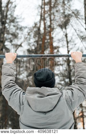 Man In Clothes Doing An Exercise On Horizontal Bar Outside In Winter. Outdoor Sports Equipment For W