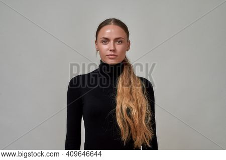 Portrait Of Beautiful Caucasian Female Model With Long Hair Wearing Black Turtleneck Looking At Came