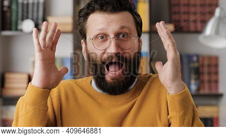 Man Is Scared, Terrified. Frightened Bearded Man In Glasses In Office Or Room In Apartment With Sudd
