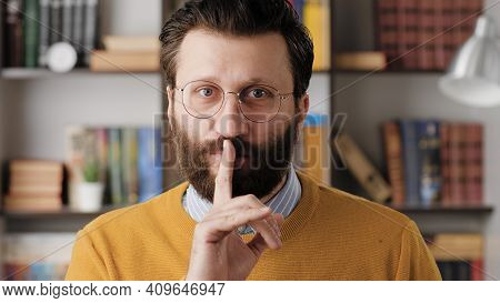Shh, Man Secret Finger. Bearded Man In Glasses In Office Or Apartment Room Looking At Camera And Bri