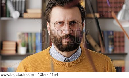 Angry Man, Rage. Angry Annoyed Bearded Man In Glasses In Office Or Apartment Room Looking At Camera