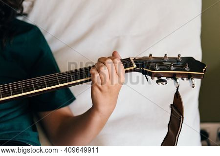 Female Hand Playing On Acoustic Guitar, Closeup
