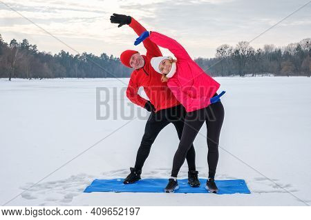 Smiling Senior Couple Warming Before Warms Up And Does Stretching Before Workout On Snowy Winter Lak