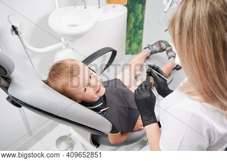 Adorable Male Child Looking At Camera And Smiling While Female Dentist Holding Dental Mirror And Exp