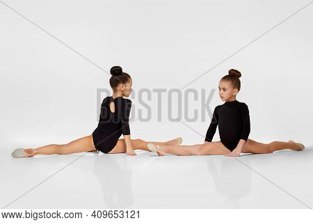 Two Young Beautiful Gymnast Girls In Black Sportswear Performs Gymnastic Poses