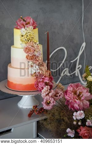 Three Layered Wedding Cake Decorated With Colorful Flowers