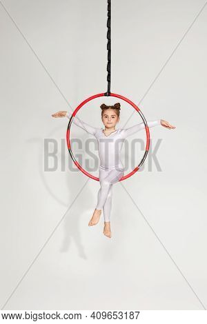 Adorable Child Girl Gymnast Shows An Acrobatic Performance On An Aerial Hoop. Acrobatics Concept.