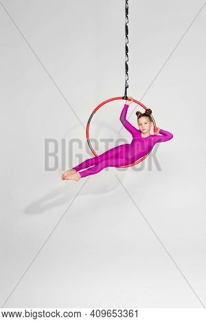 Little Child Girl Gymnast In Pink Sportwear Shows An Acrobatic Performance On An Aerial Hoop