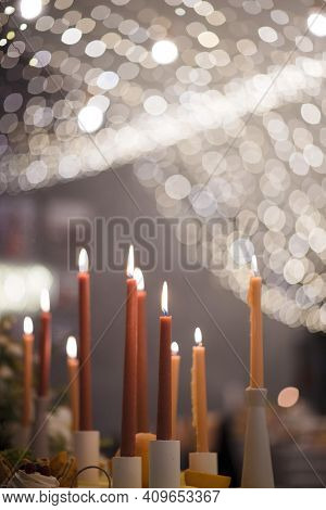 Close Up Of Many Burning Candles Standing On Wedding Table