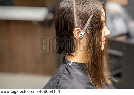 Close Up Side View Of Young Brunette Caucasian Woman With Split Hair In Sections In A Hair Salon