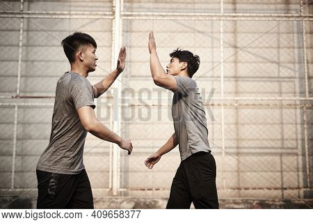 Two Young Asian Athletes Giving Hi-five Celebrating Success