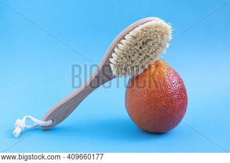 Brush For Dry Body Massage And Orange On A Blue Background Close-up. Anti-cellulite Accessory, Orang