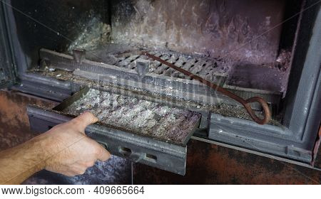 Fireplace Cleaning. Man Hand Holds A Shovel With Ash.a Hand Collects Ash From The Fireplace On An Ol