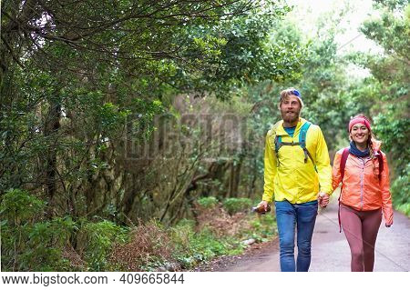 Youngs Hikers Walking. The Hikers Followed A Narrow Track Through The Forest. Holiday Concept.