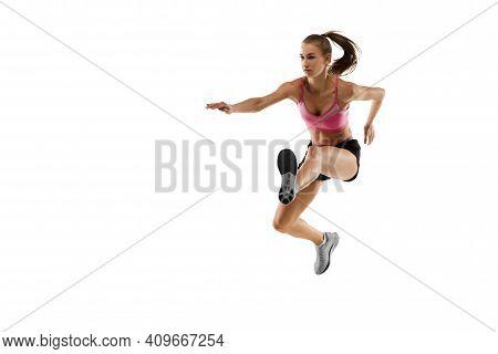 In Jump. Caucasian Professional Female Athlete, Runner Training Isolated On White Studio Background.