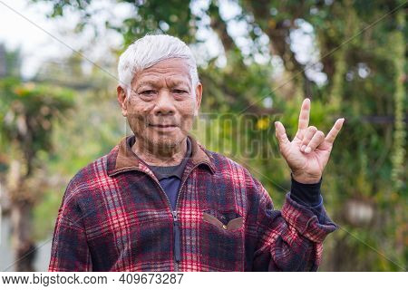 Portrait Of A Senior Man With Short Gray Hair Showing Fingers I Love You A Symbol, Smliling, And Loo