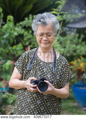 Senior Woman With Short Gray Hair Wearing Glasses And Shooting Photography By A Digital Camera At Th