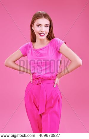 Beautiful girl fashion model poses at studio in trendy crimson suit on a pink background. Glamorous pink style.