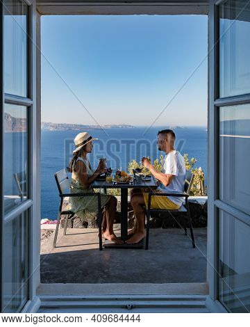 Santorini Greece, Young Couple Mid Age European And Asian On Vacation At The Greek Village Of Oia Sa
