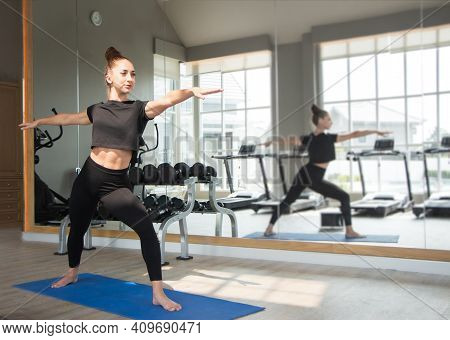 Beautiful Caucasion White Woman Doing Yoga Exercises In Fitness Gym.a Young Woman Exercising Near Th