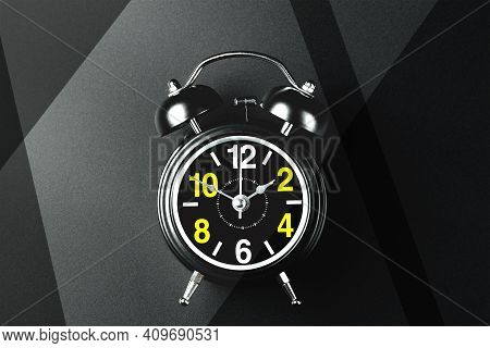 This Is A Stylish Round Alarm Clock On Metal Legs On A Dark Background. A Watch With Large Numbers O
