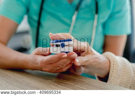 Doctor using pulse oximeter on old woman hand during appointment in clinic