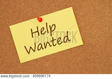 Help Wanted Message On Yellow Paper Index Card With Pushpin On Bulletin Board