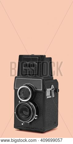 a black retro medium format film camera on a pale pink background, with some blank space on top, in a vertical format to use for mobile stories or as smartphone wallpaper