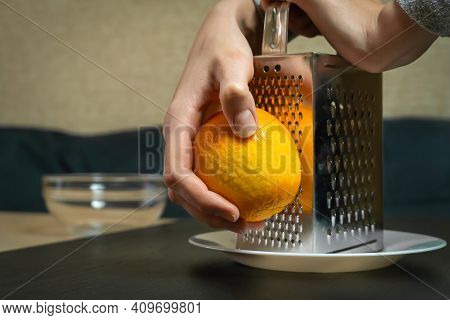 Female Chef Grates Orange Zest With A Grater Close-up In The Kitchen