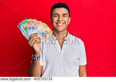 Young arab man holding swiss franc banknotes looking positive and happy standing and smiling with a confident smile showing teeth