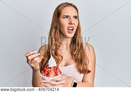 Young blonde woman eating strawberry ice cream angry and mad screaming frustrated and furious, shouting with anger. rage and aggressive concept.