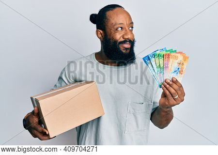 Young african american man holding delivery box and swiss franc banknotes smiling looking to the side and staring away thinking.