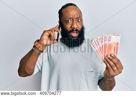 Young african american man having conversation talking on the smartphone holding norwegian krona banknotes in shock face, looking skeptical and sarcastic, surprised with open mouth