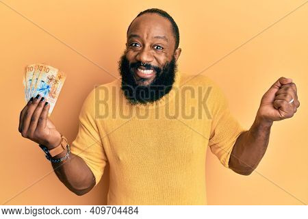 Young african american man holding 10 swiss franc banknotes screaming proud, celebrating victory and success very excited with raised arm