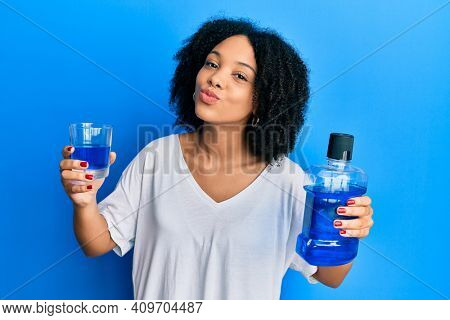 Young african american girl holding mouthwash for fresh breath looking at the camera blowing a kiss being lovely and sexy. love expression.
