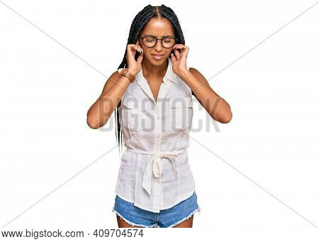 Beautiful hispanic woman wearing casual clothes and glasses covering ears with fingers with annoyed expression for the noise of loud music. deaf concept.