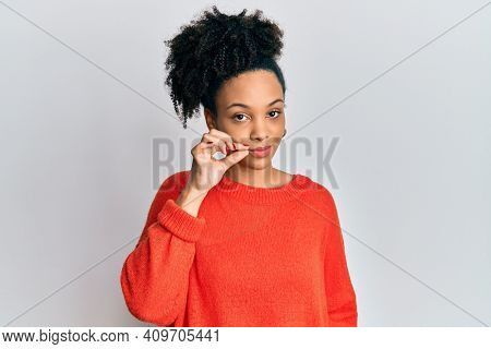 Young african american girl wearing casual clothes mouth and lips shut as zip with fingers. secret and silent, taboo talking